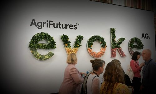 Conference attendees walking past the welcome sign in the entrance hall at evokeAG 2020.